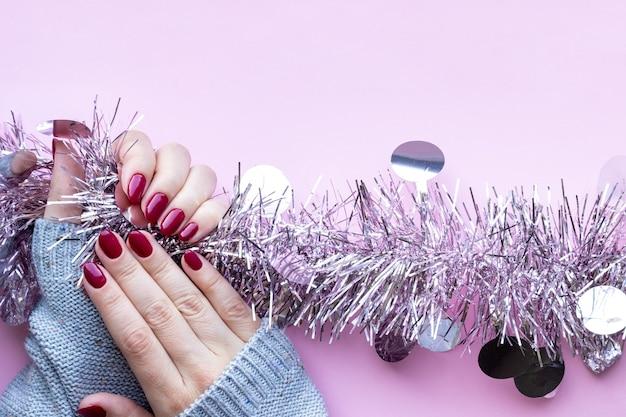 Mani femminili in maglione lavorato a maglia grigio con una bella manicure lucida
