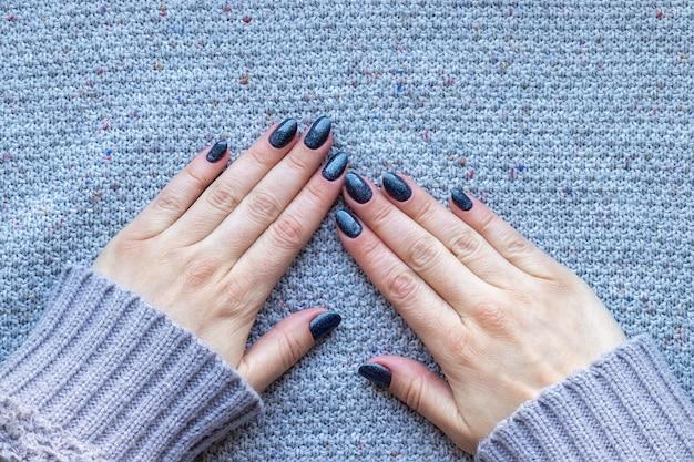 Mani femminili in maglione lavorato a maglia grigio con bella manicure - unghie scintillanti blu scuro su fondo lavorato a maglia