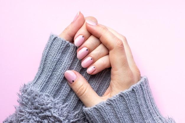 Mani femminili in un maglione lavorato a maglia grigio con manicure alla moda