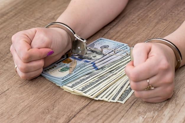 Mani femminili in manette sulle banconote in dollari