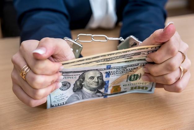 Mani femminili in manette con dollaro