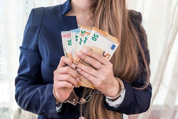 Mani femminili in manette con banconote in euro
