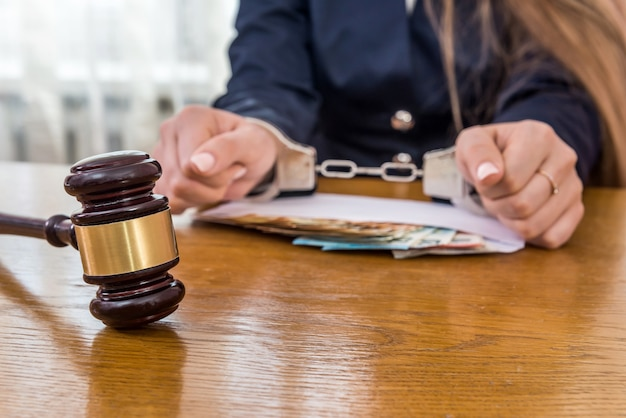 Mani femminili in manette con denaro e martelletto del giudice