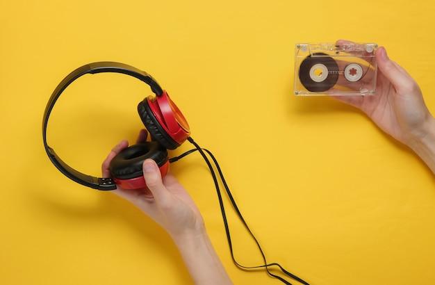 Le mani femminili tengono la cassetta audio e le cuffie