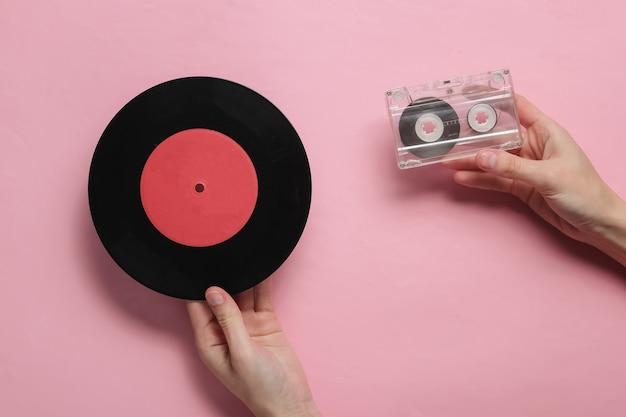 Le mani femminili tengono la cassetta audio e il disco in vinile