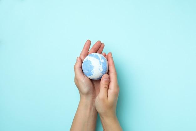 Le mani femminili tengono la palla da bagno su sfondo blu