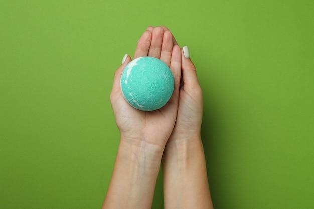 Le mani femminili tengono la palla da bagno su sfondo verde