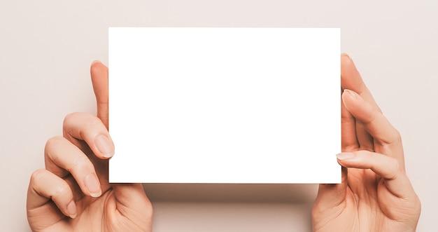 Le mani femminili tengono un foglio di carta bianco su una parete beige
