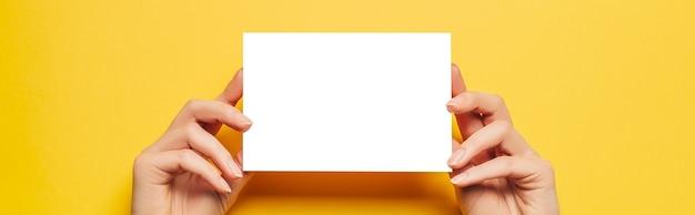 Le mani femminili tengono un foglio di carta bianco su sfondo giallo. spazio pubblicitario