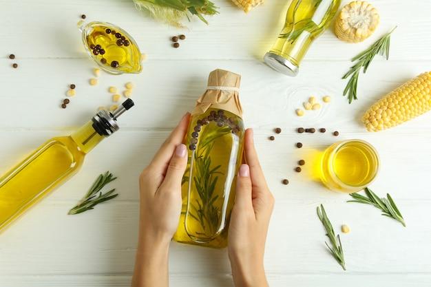 Le mani femminili tengono una bottiglia di olio su fondo di legno bianco con ingredienti