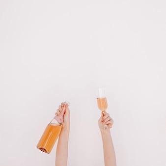 Le mani femminili tengono una bottiglia di champagne rosa e vetro contro il muro bianco. buon compleanno, festa di anniversario che celebra il concetto festivo di decorazione