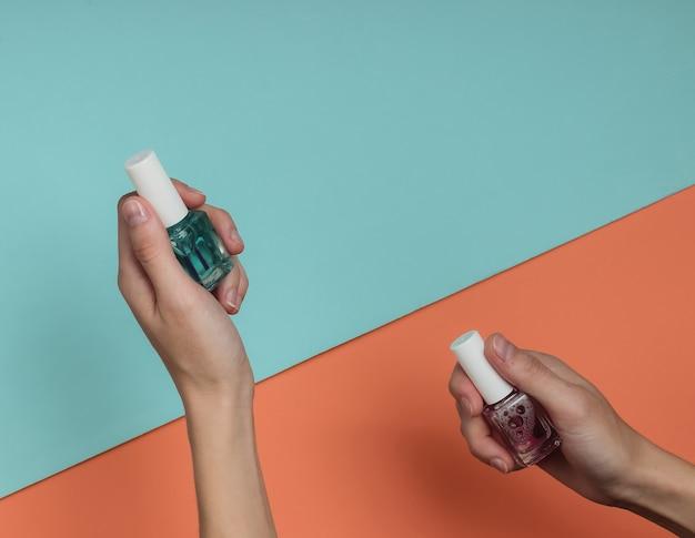 Le mani femminili tengono le bottiglie di smalto per unghie su carta colorata
