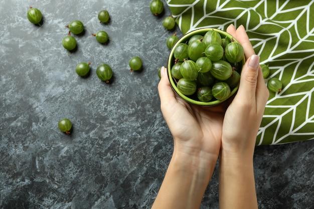Le mani femminili tengono una ciotola di uva spina su sfondo nero affumicato