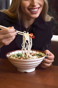 Le mani femminili tengono una ciotola con la minestra tradizionale asiatica