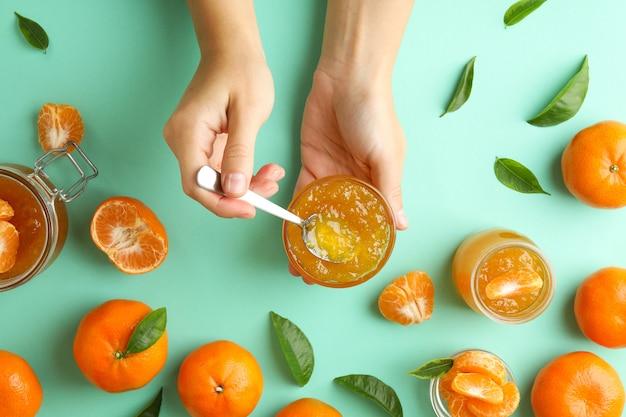 Le mani femminili tengono la ciotola con marmellata di mandarini e cucchiaio, vista dall'alto
