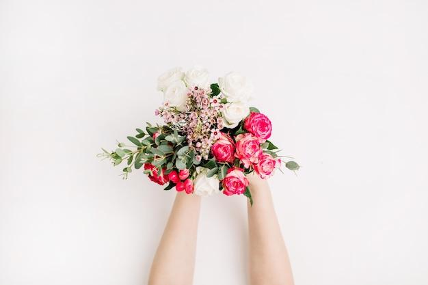 Mani femminili tengono bouquet di fiori da sposa con rose, ramo di eucalipto, fiori di campo. disposizione piatta, vista dall'alto