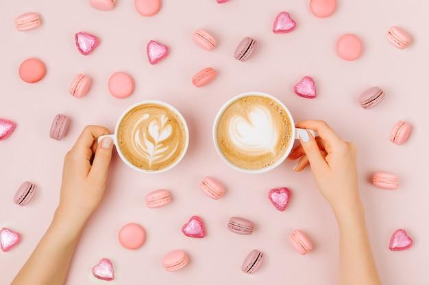 Le mani femminili tengono l'arte del cappuccino su sfondo rosa pallido