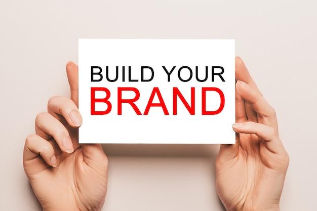Le mani femminili tengono la carta della carta con il testo build your brand su uno spazio giallo