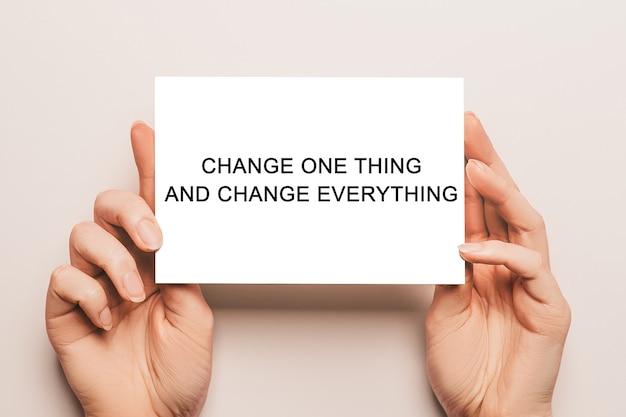 Le mani femminili tengono la carta della carta con il testo cambia una cosa e cambia tutto su uno spazio giallo