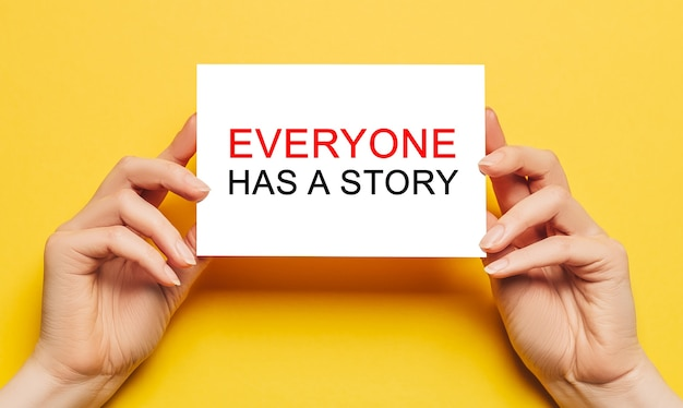 Le mani femminili tengono la carta con il testo ognuno ha una storia su uno sfondo giallo. concetto di affari e finanza