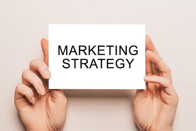 Le mani femminili tengono la carta con testo strategia di marketing su sfondo giallo. concetto di affari e finanza