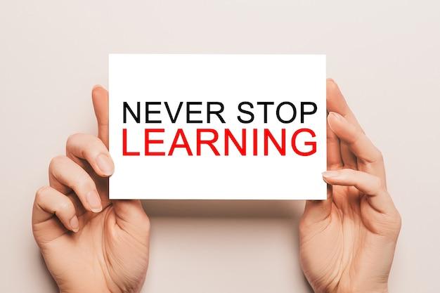 Le mani femminili tengono la carta con il testo never stop learning su uno sfondo giallo. istruzione e concetto di studio