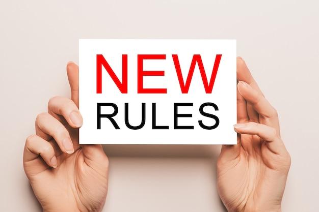 Le mani femminili tengono la carta della carta con le nuove regole del testo su una parete gialla