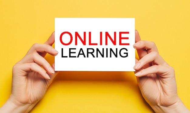 Le mani femminili tengono la carta con testo di apprendimento online su uno sfondo giallo. istruzione e concetto di studio