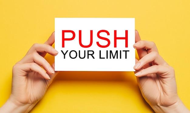 Le mani femminili tengono la carta della carta con il testo push your limit su un muro giallo