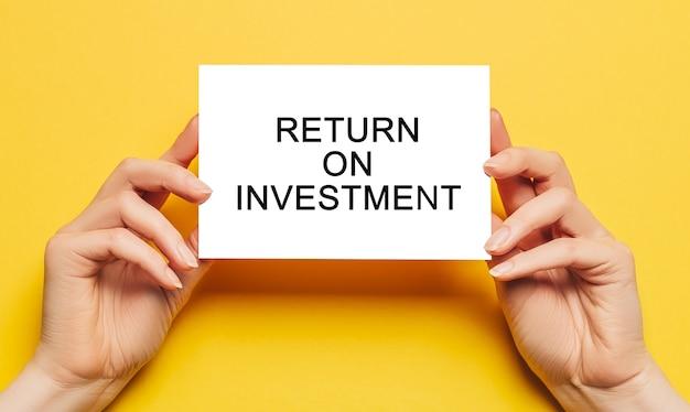 Le mani femminili tengono la carta con testo return on investment su uno sfondo giallo. concetto di affari e finanza
