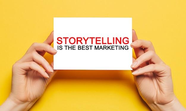 Le mani femminili tengono la carta con il testo la narrazione è il miglior marketing su uno sfondo giallo. concetto di affari e finanza