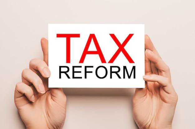Le mani femminili tengono la carta con la riforma fiscale del testo su uno sfondo giallo. concetto di affari e finanza