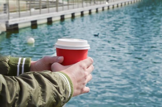 Le mani femminili tengono una tazza di cartone con caffè sul molo sul mare.