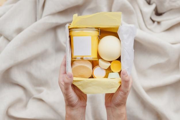 Le mani femminili tengono il set di scatole per la cura di cosmetici ecologici, scrub al sale da bagno, sapone fatto a mano, spugna per lavare...