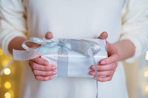 Le mani femminili tengono la scatola regalo di natale o capodanno su sfondo boke natale capodanno comple...
