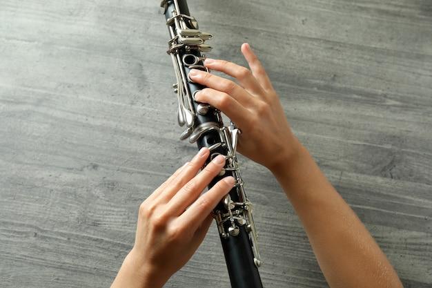 Le mani femminili tengono il clarinetto su fondo strutturato grigio