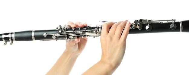 Le mani femminili tengono il clarinetto, isolato su sfondo bianco