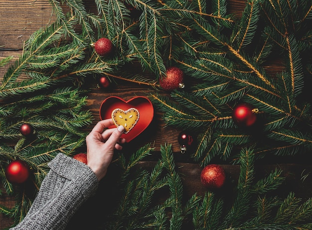 Le mani femminili tengono il biscotto accanto ai rami e alle bagattelle dell'albero di natale intorno