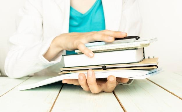 Le mani femminili tengono i quaderni, isolati su priorità bassa bianca