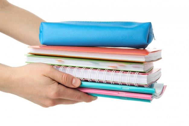 Le mani femminili tengono i quaderni, isolati