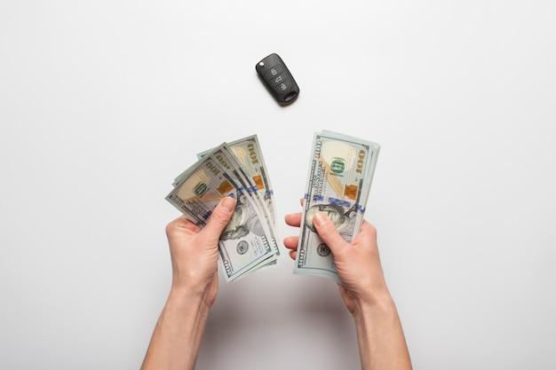 Le mani femminili tengono, conta soldi, dollari su uno sfondo chiaro con una chiave di auto. concetto di retribuzione, acquisto, tasse, affitto, leasing.