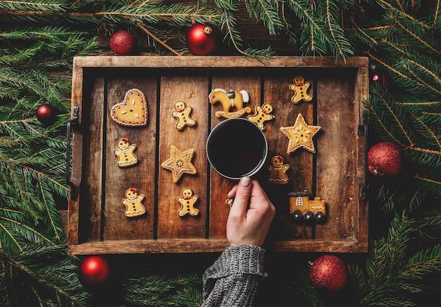 Le mani femminili tengono la tazza di tè accanto ai biscotti e all'albero di natale sul vassoio