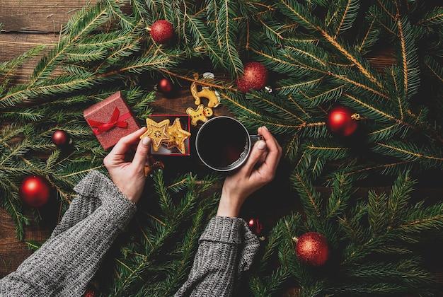 Mani femminili tengono tazza di tè e biscotti con albero di natale su un tavolo