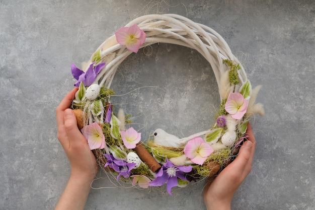 Le mani femminili tengono una corona di pasqua con fiori e un uccello su un tavolo grigio. concetto di primavera decorazione della casa.
