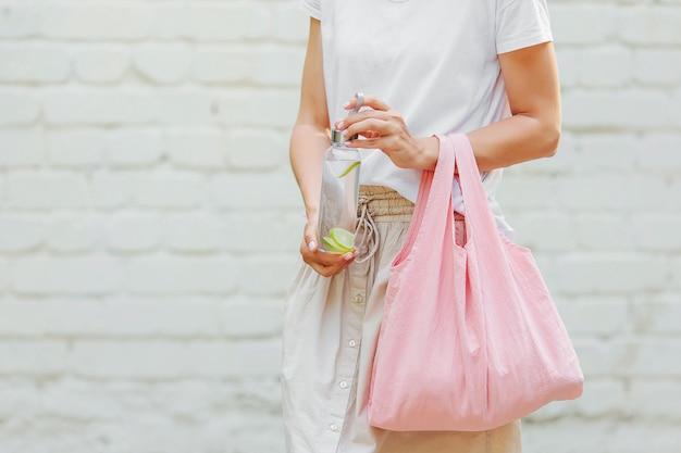 Le mani femminili tengono la borsa ecologica e la bottiglia d'acqua riutilizzabile. zero sprechi. concetto di stile di vita sostenibile.