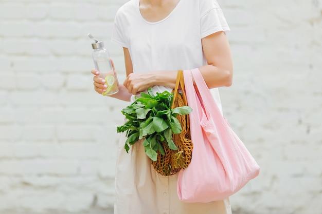 Le mani femminili tengono un sacchetto ecologico di verdure, verdure e una bottiglia d'acqua riutilizzabile. zero sprechi. concetto di stile di vita sostenibile.