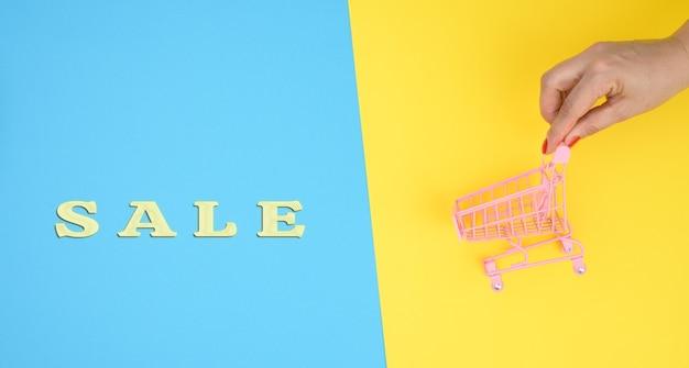 Le mani femminili tengono un carrello in miniatura di metallo vuoto su sfondo blu. concetto di vendita, sconti stagionali, spazio copia