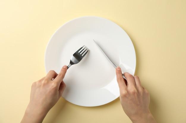 Le mani femminili tengono la forcella e il coltello su fondo beige con il piatto, vista superiore