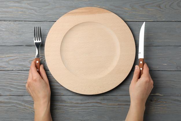 Le mani femminili tengono la forcella e il coltello su di legno con il piatto, vista superiore