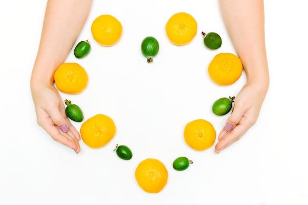 Le mani femminili tengono i mandarini freschi e il feijoa a forma di cuore su bianco